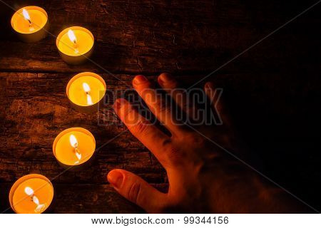 Lighted Candles And Hand On A Wooden Background