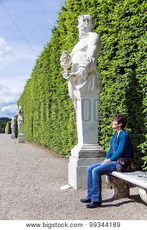 Womans Sitting Beside Ornamental Statue In Garden Palace Versailles, Paris