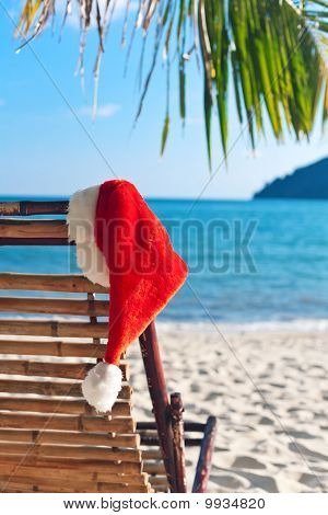 Red Santa's Hat Hanging On Beach Chair Under Palm Tree