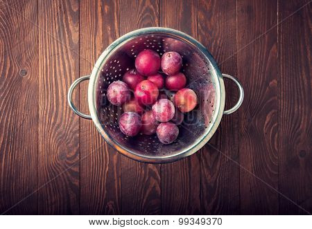 Fresh ripe plums on wooden board