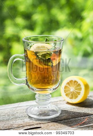 Tea With Lemon And Mint In A Glass Mug On A Light Wooden Background
