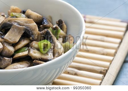 Mushroom Vegetable Dish In A White Bowl On A Bamboo Mat, Closeup