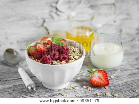 Oatmeal With Summer Berries - Raspberries, Strawberries, Honey And Yogurt In A White Bowl On A Light