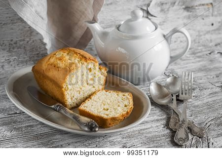 Simple Cake On An Oval Platter, A Teapot And Silver Cutlery On A Light Wooden Background