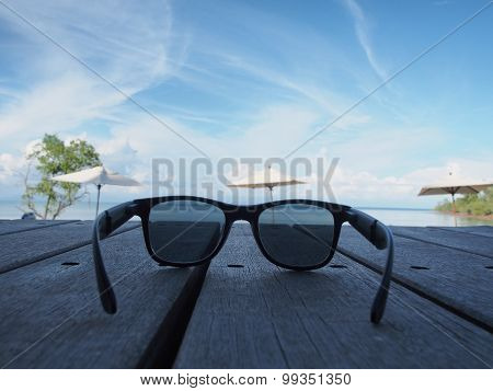Black Sunglasses Placed On A Wooden Board At The Beach.