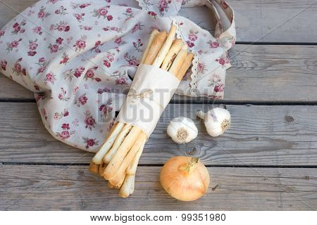 breadsticks on Wooden background with garlic, onions and bags