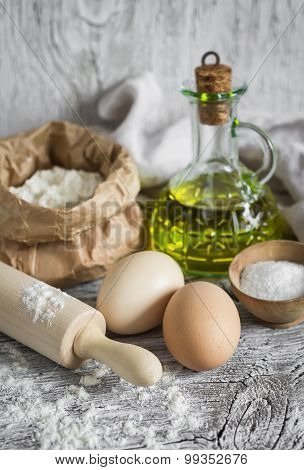 Flour, Eggs, Olive Oil - Ingredients To Prepare The Dough For Pasta On A Light Wooden Surface