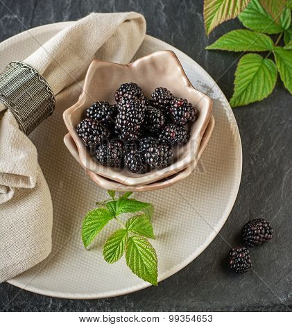 Fresh ripe blackberries in ceramic cups handmade pottery are served for breakfast