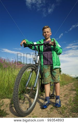 Young Boy With A Bicycle In Nature Rests.