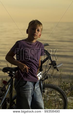 Boy On A Bicycle Near The Sea In The Evening At Sunset.