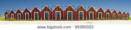 Panoramic View Of Row Of Red Wooden Boathouses