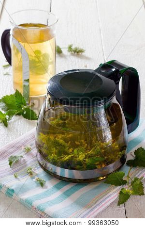 Teapot And Cup Of Herbal Tea With Fresh Mint Flower On A Wooden Table