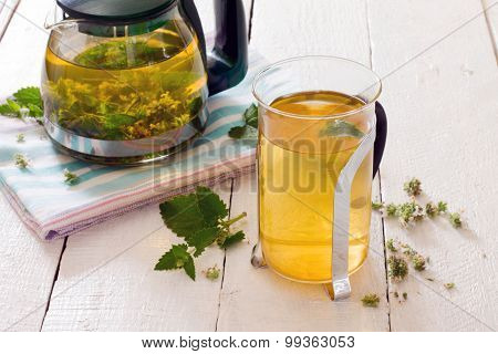Teapot And Cup Of Herbal Tea With Fresh Mint Flower