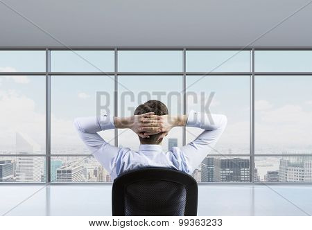 Rear View Of The Relaxing Businessman Is In A Modern Panoramic Office. New York Cityscape.
