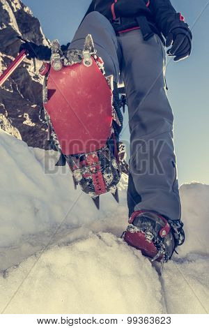 Close up of hiking shoes with crampons and ice axe.