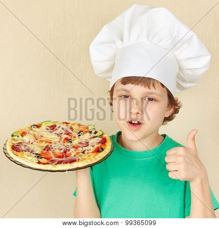 Little smiling kid in chefs hat with cooked appetizing pizza