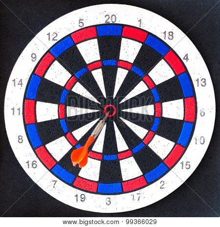 Dart board with one red dart in the middle