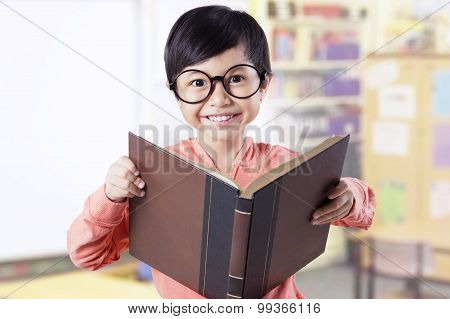 Adorable Kid Holding Textbook In Classroom