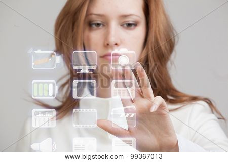 Young businesswoman pressing high tech type of modern multimedia buttons on a virtual background