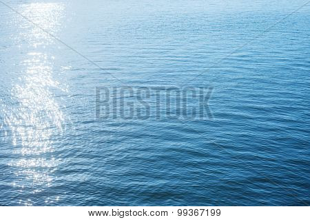 good blue background of water with sun reflections
