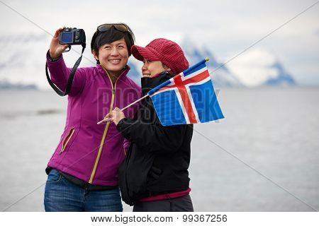 Young asian women taking selfie in beautiful westfjords iceland landscape, waving flag carefree holiday vacation