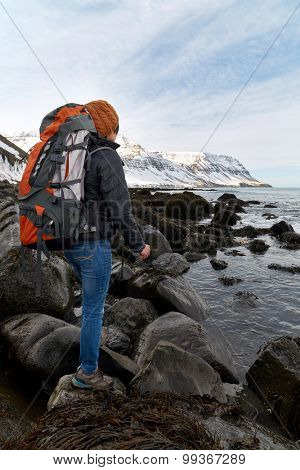 Asian woman traveler hiking with backpack along the ocean with large rocks, focus stacking technique