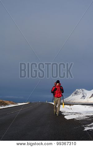 Backpacker travelling holiday on a budget hitchhiking for a ride on empty road, in harsh winter snowy cold extreme conditions