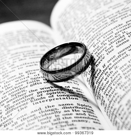 wedding ring balanced on the love chapter of the bible