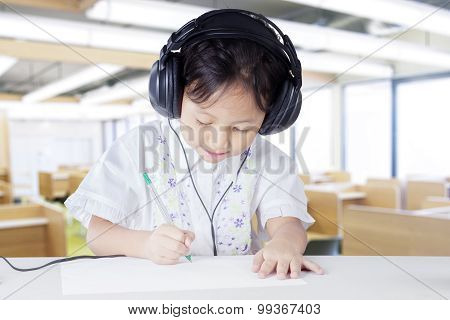 Child Wearing Earphones In Listening Lesson