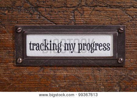 tracking my progress - a label on a grunge wooden file cabinet