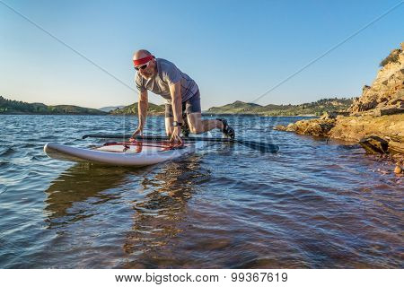 male paddler starting stand up paddling on a rocky shore of Horsetooth Reservoir, Fort Collins, Colorado, summer scenery