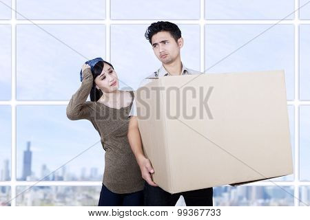 Confused Couple Bring Box At Apartment