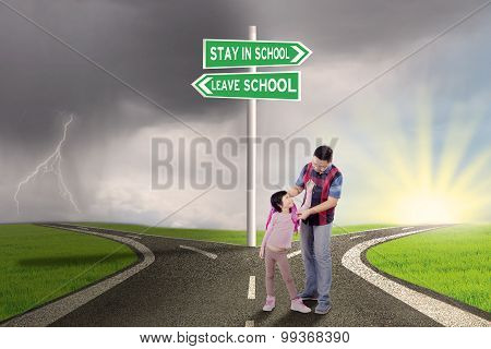 Girl And Dad With Road Sign To Stay Or Leave School