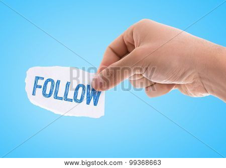 Piece of paper with the word Follow with blue background
