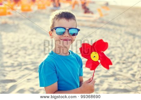 Little Boy With Pinwheel On Beach