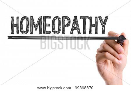 Hand with marker writing the word Homeopathy