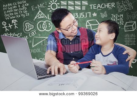 Male Student Talking With His Tutor In The Class