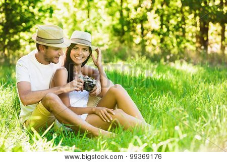 Happy smiling couple relaxing on green grass. Summer day