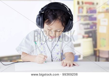 Primary School Student Studying In Class With Headset