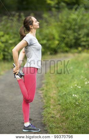 Workout in a Park. Young sporty woman doing exercise warm-up before Jogging in park in sunshine on beautiful summer day. Sport fitness model caucasian ethnicity training outdoors.