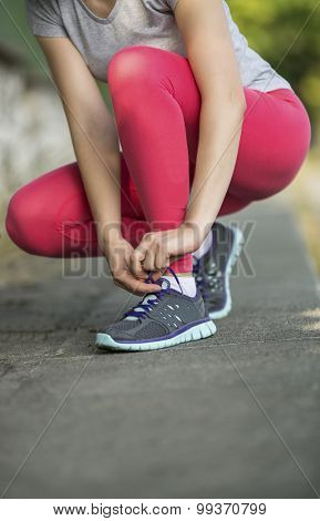 Workout in a Park. Young sporty woman tying running shoe laces before Jogging in park in sunshine on beautiful summer day. Sport fitness model caucasian ethnicity training outdoors.