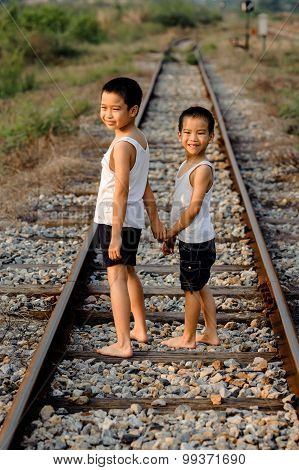 Two Boys Walk On The Railway