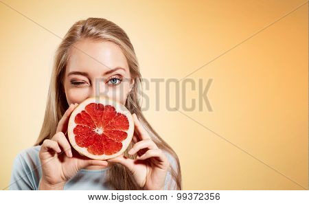 Young Blonde Woman With Grapefruit In Her Hands Studio Portrait Isolated On Orange Background. Young