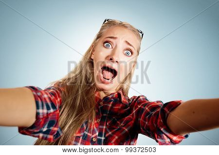 Close Up Portrait Of A Young Shocked Blonde Girl Holding A Smartphone Digital Camera With Her Hands