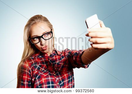 Close Up Portrait Of A Young Kissing Blonde Girl Holding A Smartphone Digital Camera With Her Hands