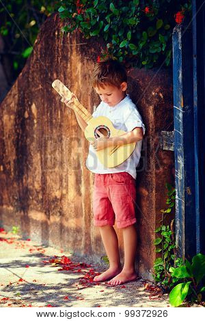 Cute Young Boy Playing Guitar Near The Summer Old Fence