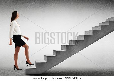 smiley businesswoman in formal wear walking up concrete stairs over light grey background