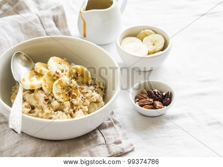 Oatmeal With Banana, Caramel Sauce And Pecans In A White Bowl On A Light Surface, A Delicious And He