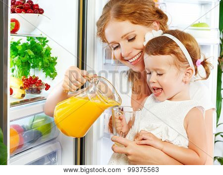Happy Family Mother And Baby Daughter Drinking Orange Juice In  Kitchen Near Refrigerator