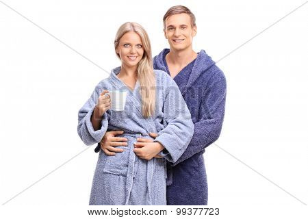 Studio shot of a young handsome couple in blue bathrobes posing together isolated on white background